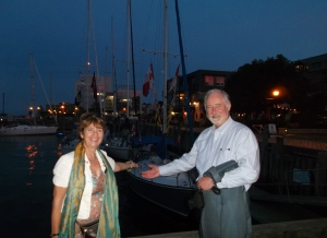 Gwen and Peter point to a sailboat 'decked out' for Canada Day just before a festive eve of fireworks commences over the harbour.