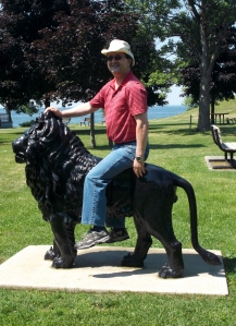 Brother Edwin has a  more stately demeanor while astride the stately historic lion in MacDonald Park.