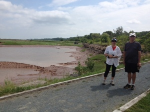 Gwen and Cousin Dwight take a breather on  the trail passes through Wolfville and other towns in the area.  it is set up on an old rail road track.  The tide is out at this time, and all is peaceful!  Photo taken by Patricia.