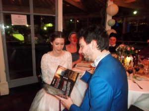 Carole and Gildas admire the gift from all of us:  a  published collection of our favourite recipes!